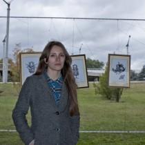 Мария Вдовиченко на фот\не своих работ на выставке +/-15.