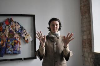 Куратор выставки Елена Червоник на фоне работы Маши Шубиной